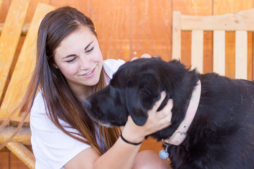 A girl at New Haven smiling and petting a dog