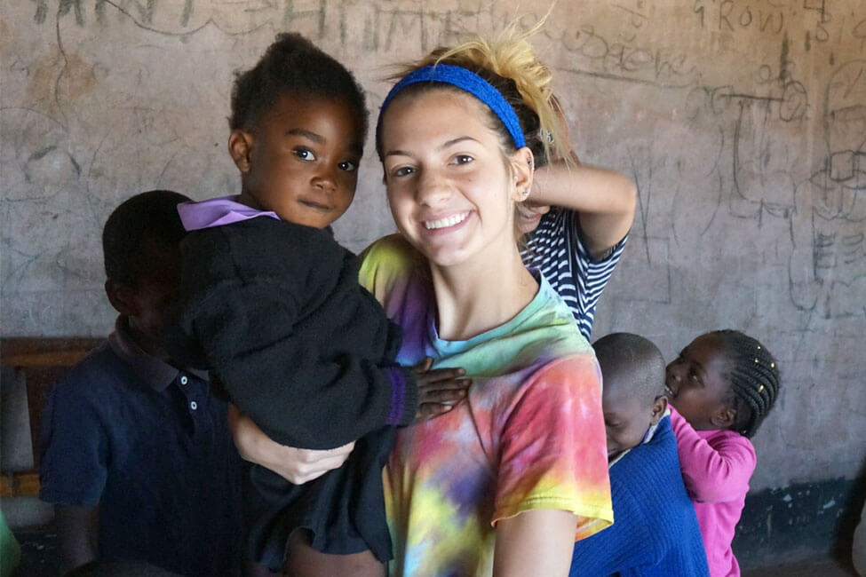 A New Haven Student Smiling with a child in Zambia
