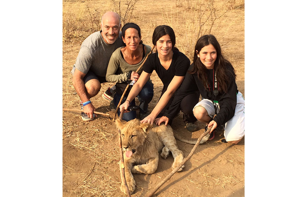 Family pictured with a baby lion on New Haven's trip to Zambia