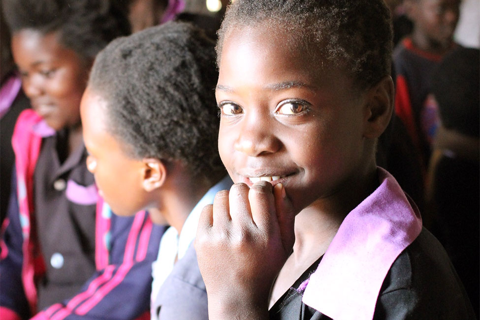A girl from Zambia smiling at the camera